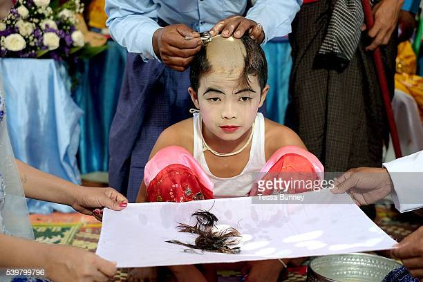 Family members shave the boys head and the hair is caught in a white cloth held by their parents at a Shinbyu Novice Ceremony on 28th March 2016 in...