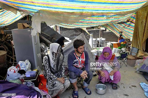 A family members sitting in their damaged house as their houses are submerged in flood waters on September 11 2014 in Srinagar India More than 50000...