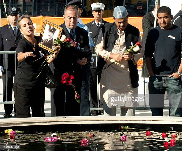 Family members stand at the reflecting pool at Ground Zero during the annual 9/11 memorial service September 11 2010 in New York City People gathered...