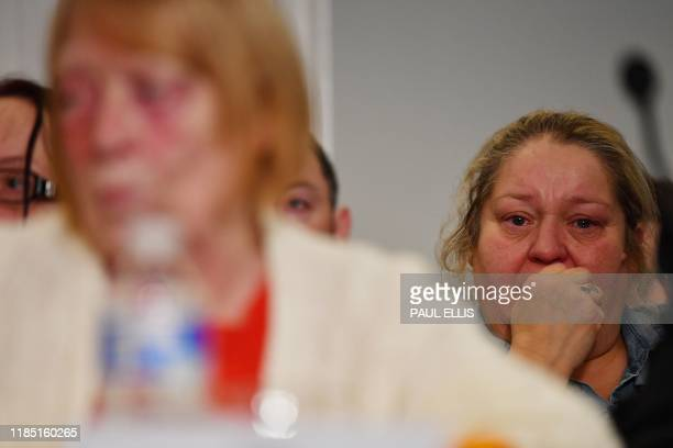 Family members survivors and campaigners for the victims of the Hillsborough Disaster react during a press conference in Liverpool northwest England...