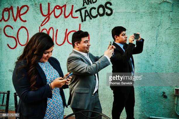 Family members taking photos with smart phones during celebration dinner on restaurant deck
