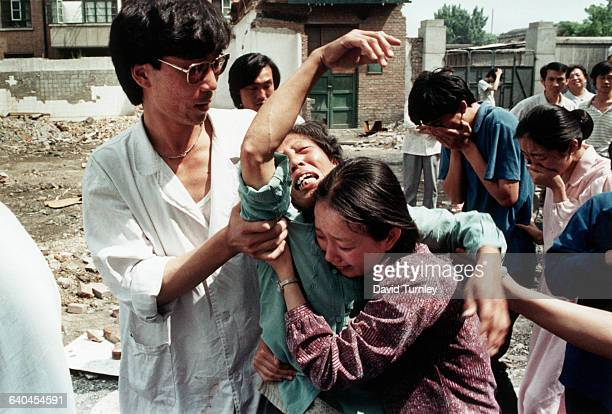 Family members try to comfort a griefstricken mother who has just learned of the death of her son a student protester killed by soldiers at Tiananmen...