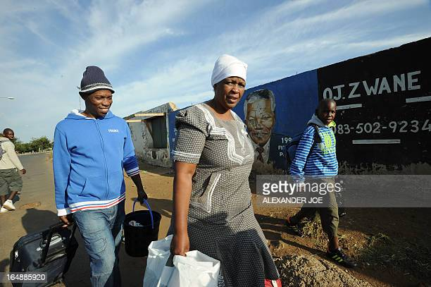 Family members walk to a bus stop past a wall bearing painted portraits of former South African President Nelson Mandela in Soweto on March 29 2013...