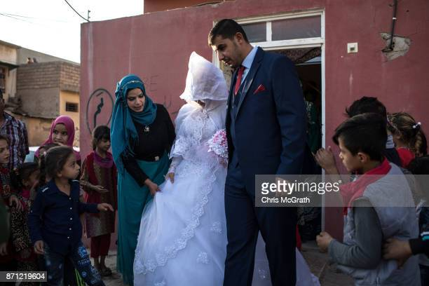 Family members watch on as a bride and groom leave their house to be married in West Mosul on November 3 2017 in Mosul Iraq Five months after Mosul...