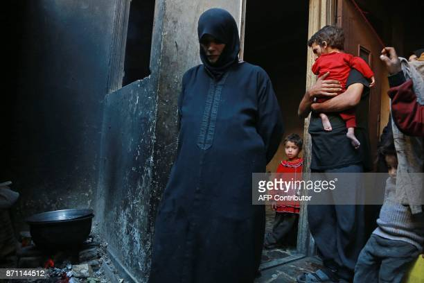 Family members watch on as Umm Saeed prepares a meal in the family's kitchen on November 6 2017 in Saqba in the besieged rebelheld Eastern Ghouta...