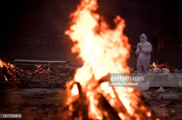 Family members wearing PPE perform the last rites for a person who died of Covid-19 at a crematorium on May 09, 2021 in New Delhi, India. India broke...