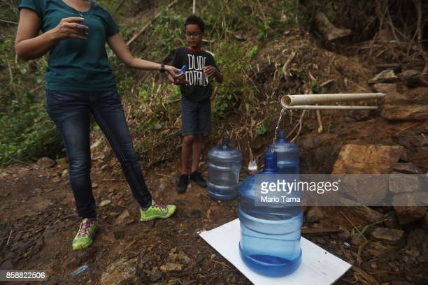 Family members whose home no longer has running water collect spring water flowing from a mountain more than two weeks after Hurricane Maria hit the...