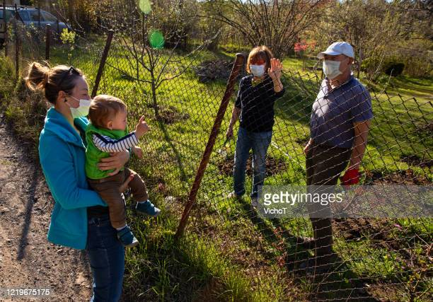 family members with protective masks communicating across a fence outside the city - small group of people stock pictures, royalty-free photos & images