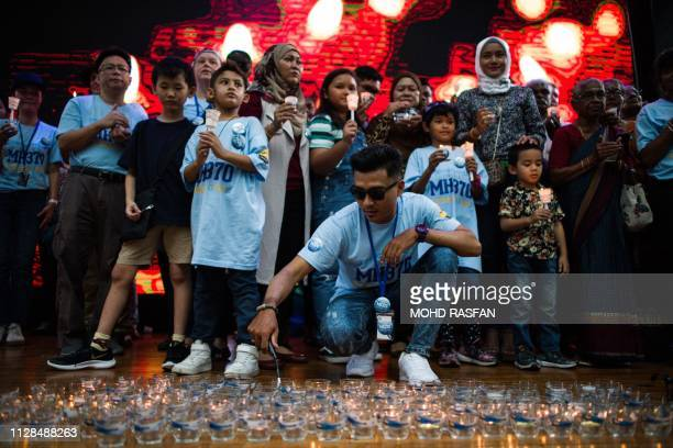 Family members with unaccounted for loved ones hold lit candles during a memorial event ahead of the fifth anniversary of the missing Malaysia...
