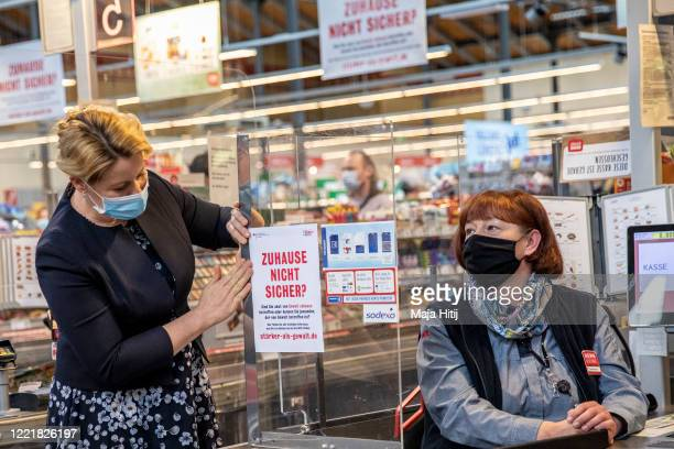 Family Minister Franziska Giffey places a poster next to the cashier Kerstin Strasen during a launch of the campaign Not safe at home against...