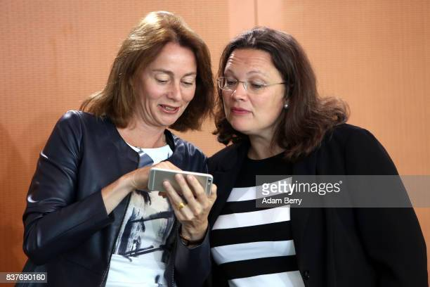 Family Minister Katarina Barley looks at a mobile phone with Minister of Work and Social Issues Andrea Nahles as they arrive for the weekly German...
