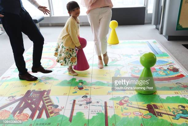 """Family models Him Wong Emily Suen and fiveyearold daughter Alexa pose for a picture at 'Giant Hong Kong Board Game"""" part of """"Yesterday once..."""