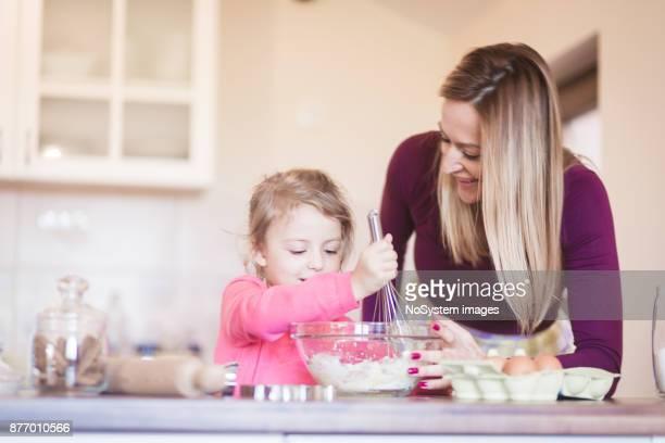 家族の瞬間。クッキーを作って台所で楽しい時を過す彼女の母親と一緒に幸せな若い女の子。