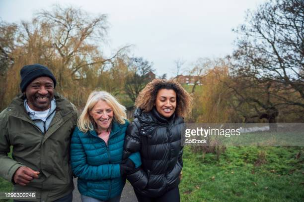 family morning walk through the park - multiracial group stock pictures, royalty-free photos & images