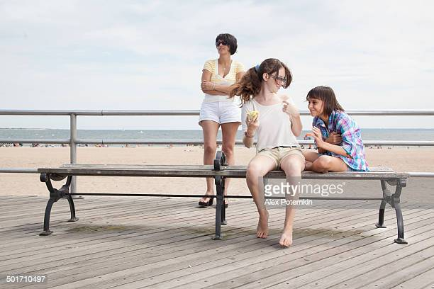 Family, mother and two daughters, at the bench at boardwalk