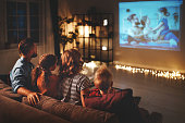 family mother father and children watching projector, TV, movies with popcorn in   evening   at home