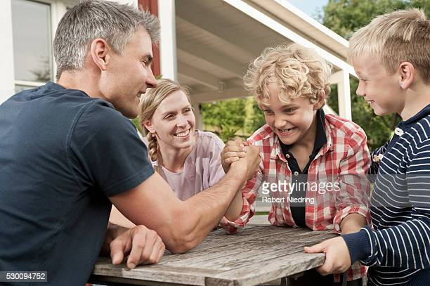 Family mother father kids boy arm wrestling