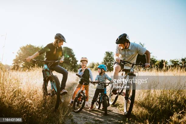 family mountain bike riding together on sunny day - outdoors stock pictures, royalty-free photos & images