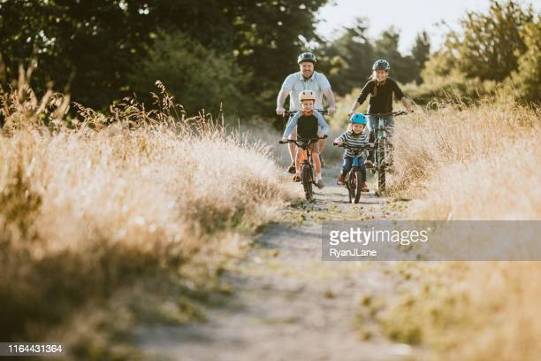 family mountain bike riding together on sunny day - cycling helmet stock pictures, royalty-free photos & images
