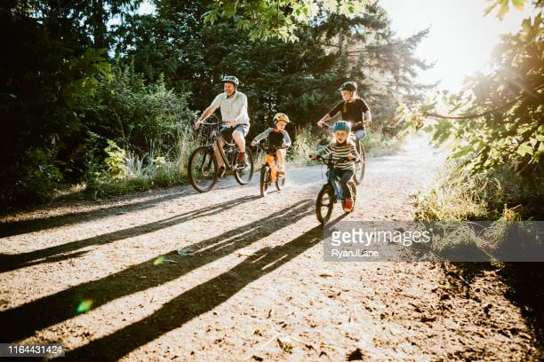 family mountain bike riding together on sunny day - weekend activities stock pictures, royalty-free photos & images