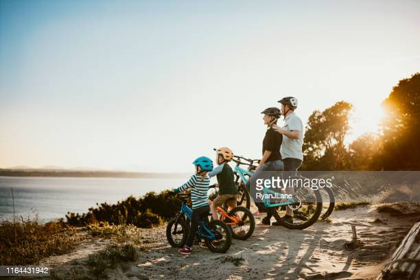 family mountain bike riding together on sunny day - pacific ocean stock pictures, royalty-free photos & images