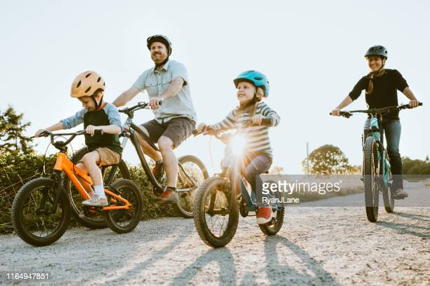 family mountain bike riding together on sunny day - sports helmet stock pictures, royalty-free photos & images