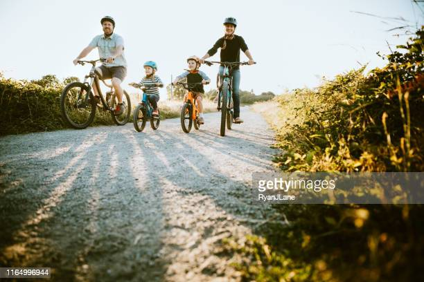 family mountain bike riding together on sunny day - estilo de vida ativo imagens e fotografias de stock