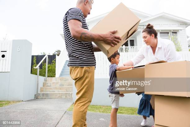 Family move boxes into their new home
