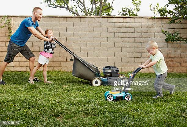 Family mowing lawn in backyard