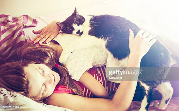Family napping with loving cat