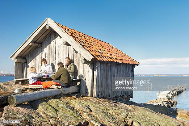 Family near wooden building at sea