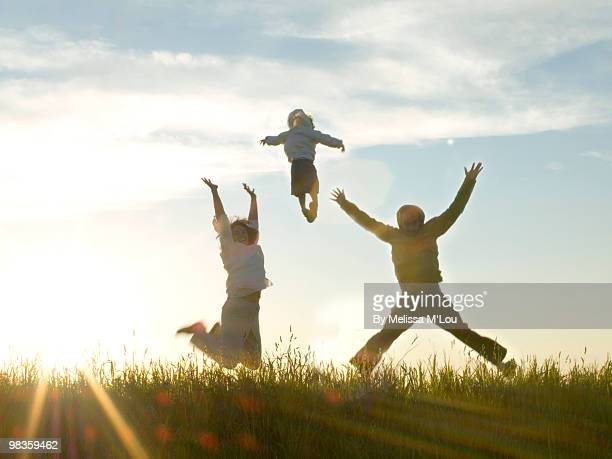 Family of 3 jumping in field at sunset