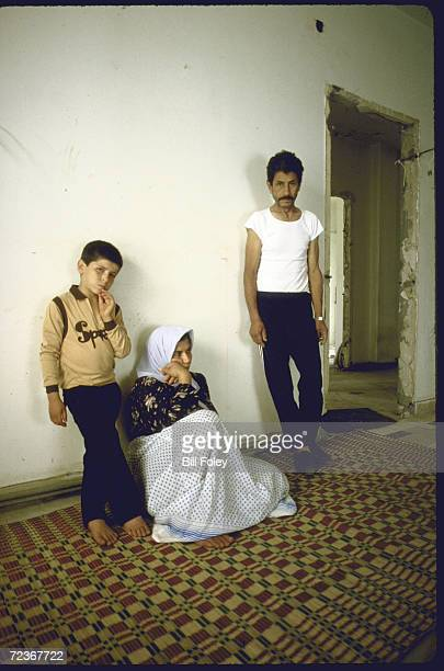 Family of 3 refugees from fighting in camps posing in their new home amid wreckage at old US Embassy car bombed in 4/83 on Corniche