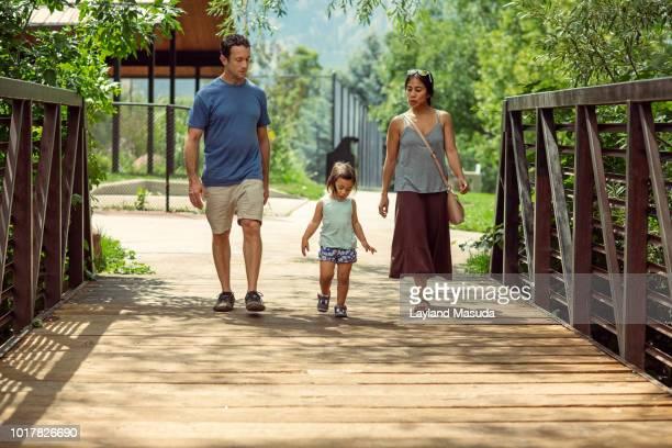 family of 3 walking across a bridge - girls with short skirts - fotografias e filmes do acervo