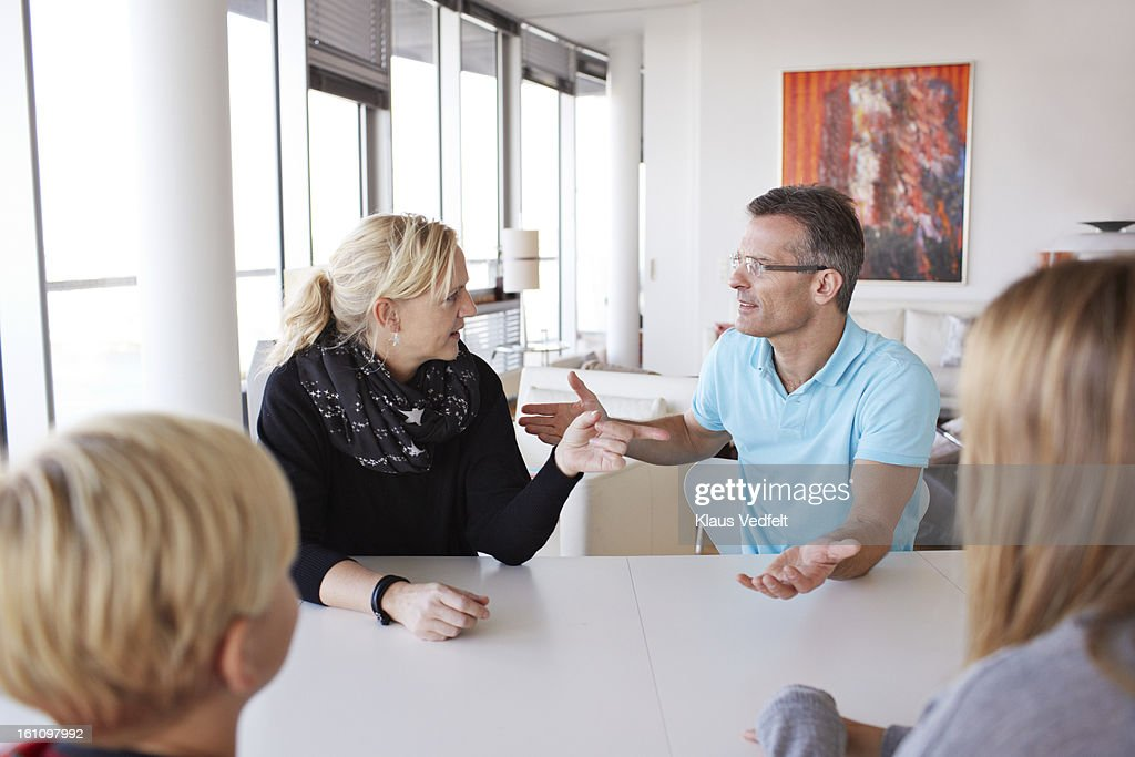 Family of 4 having a discussion at dinner table : Stock Photo