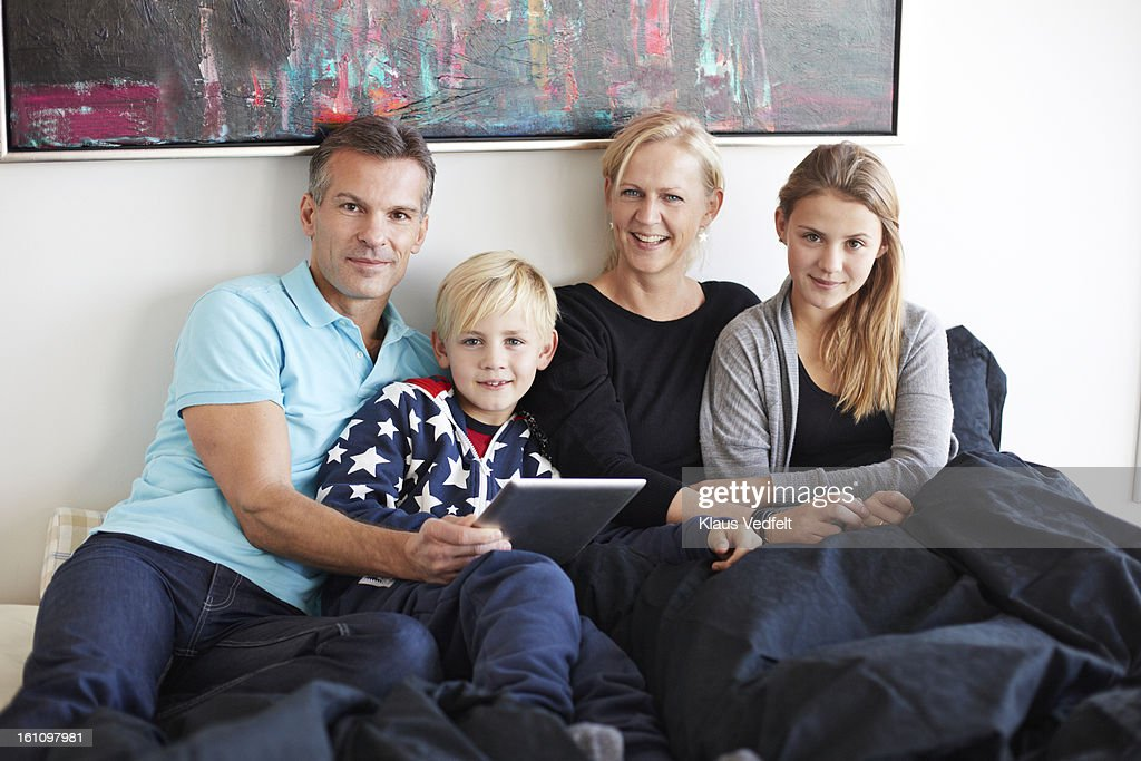 Family of 4 looking at tablet in bedroom : Stock Photo