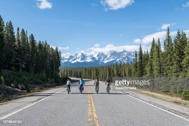 family of bicyclists ride on mountain road - family with one child stock pictures, royalty-free photos & images