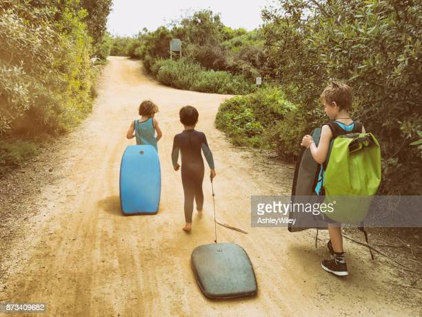 family of boys walk to the beach together while carrying their boogie boards - santa barbara stock photos and pictures