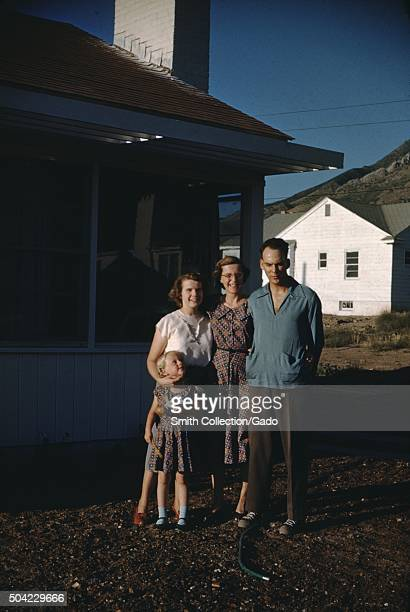 Family of Christian missionaries a father mother daughter and young son standing in partial shade in front of a plain white house in Salt Lake City...