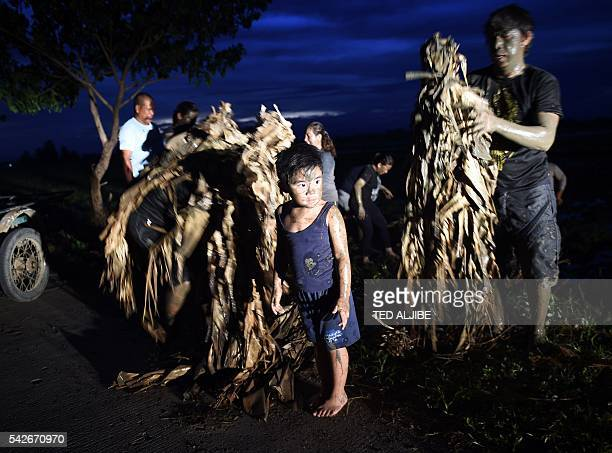 A family of devotees cover their bodies and costumes made of banana leaves with mud prior to heading for the church to attend mass as part of a...