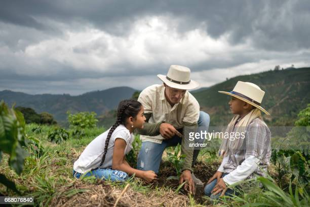 Family of farmers planting a tree at the farm