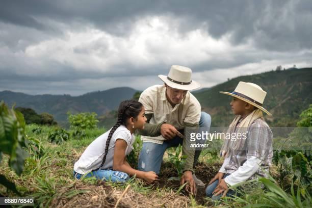familia de agricultores plantando un árbol en la granja - campesino fotografías e imágenes de stock