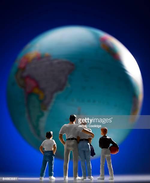 Family of figurines gazing at world globe