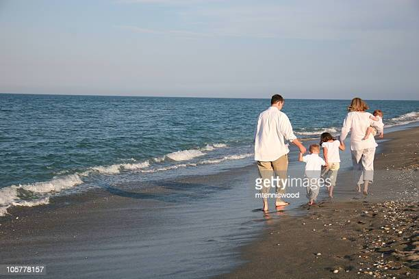 Family of five dressed in white walking on a beach