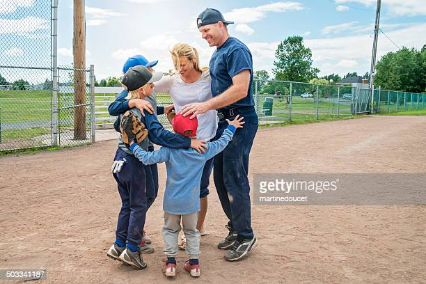 family of five in a group hug after baseball game. - baseball mom stock pictures, royalty-free photos & images