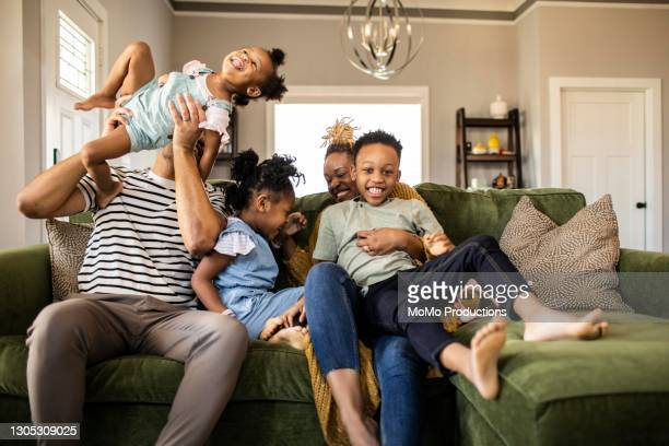 family of five playing on sofa at home - lifestyle stock pictures, royalty-free photos & images