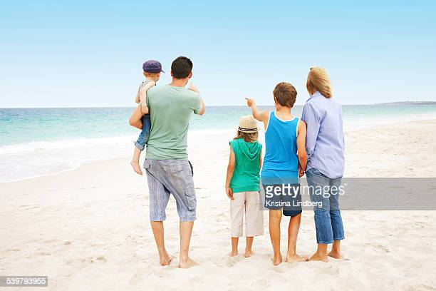 Family of five pointing to the sea