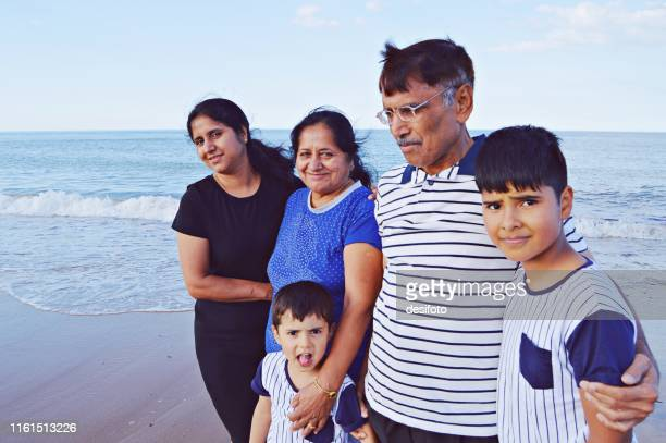 a family of five posing casually in a cheerful mood at a sandy beach - five people stock pictures, royalty-free photos & images