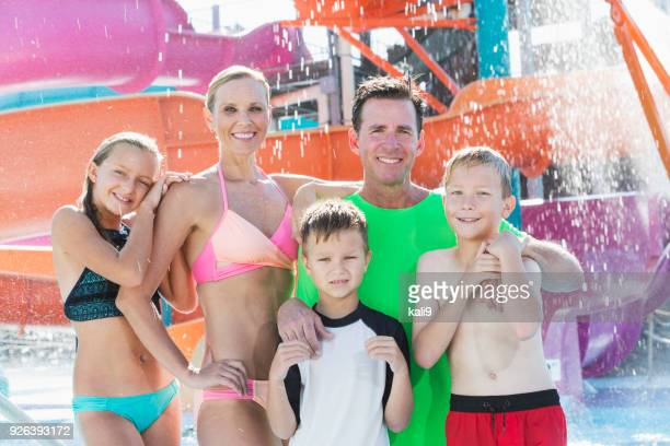 Family of five posing in front of waterslide at water park