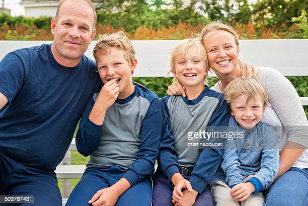 Family of five posing on bench after a baseball game.